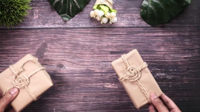 man hand ta hemgjord utformad presentförpackning på bordet - recycling heart bildbanksvideor och videomaterial från bakom kulisserna
