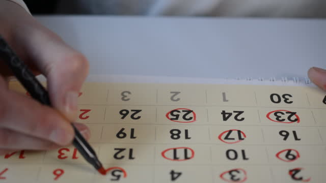 Man hand crossing out days on calendar video
