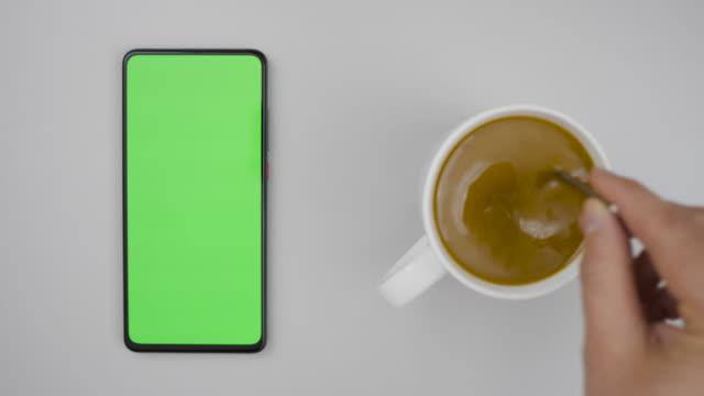 人手杯熱咖啡和使用智慧手機觀看綠屏頂視圖。智慧手機與綠色類比螢幕業務概念。人手攪拌咖啡與勺子在桌子上。慢動作。 - 模板 個影片檔及 b 捲影像