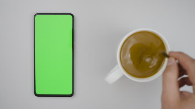 Man Hand Cup of Hot Coffee and Using Smartphone Watching Green Screen Top View. Smartphone with Green Mock-up Screen Business Concept. Person Hand Stirring Coffee with Spoon on Table.
