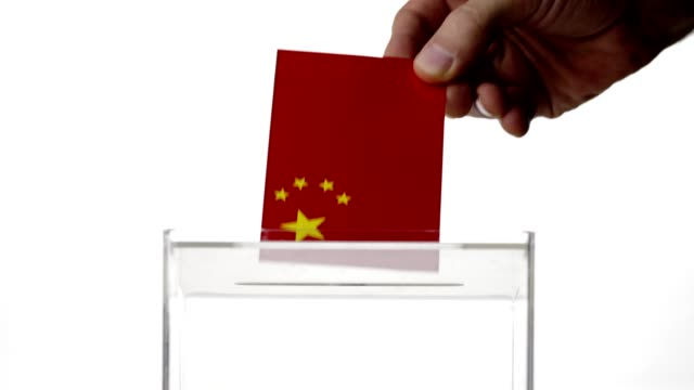 Man hand dropping Chinese flag into voting ballot