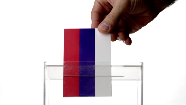 Man hand dropping France flag into voting ballot