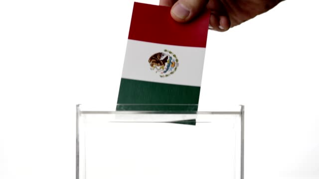 Man hand dropping Mexican flag into voting ballot