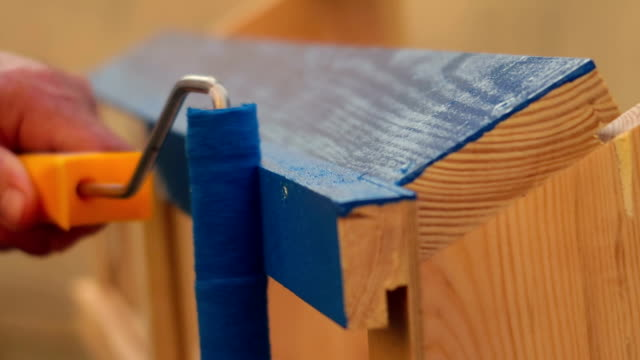 Man hand hold paint roller and paint / renovate a wooden furniture in blue at home, close-up. Man hand hold paint roller and paint / renovate a wooden furniture in blue at home, close-up, blur effect, bokeh renovation stock videos & royalty-free footage