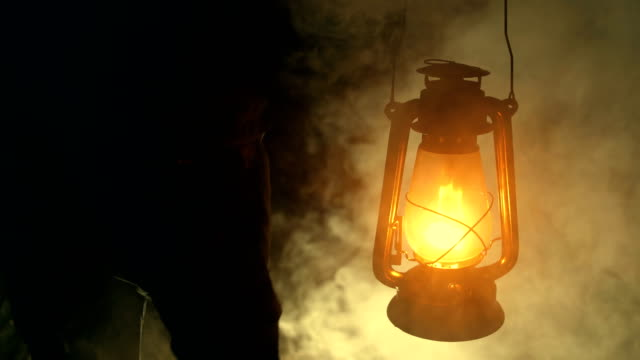 man hand holding a kerosene lamp at night - lanterna attrezzatura per illuminazione video stock e b–roll
