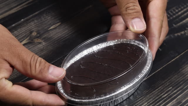 man hand holding and chocolate cake in plastic box