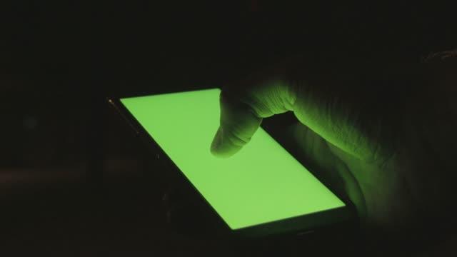 Man hand holding smartphone in night city, chroma key screen