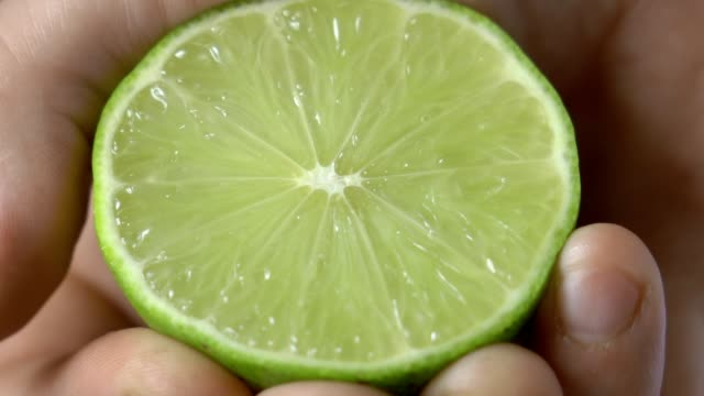 Man hand presses a lime on kitchen video