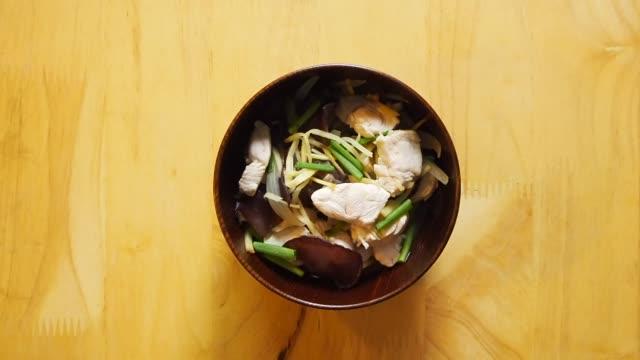 vídeos de stock, filmes e b-roll de mão do homem põr uma bacia de gengibre da galinha na tabela de madeira - fine dining