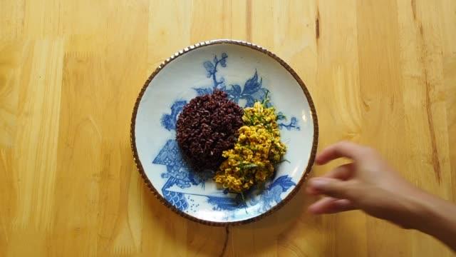 vídeos de stock, filmes e b-roll de mão do homem põr um prato da carne de porco picante da fritada do stir com ervas na tabela de madeira - fine dining