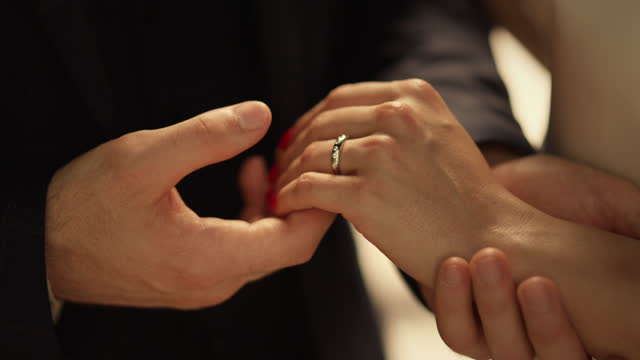 Man hand putting ring on girl finger. Unknown man taking woman hand outdoors Closeup unknown man taking woman hand outdoors. Man hand putting ring on girl finger. Newlywed couple exchanging rings on wedding ceremony. Unrecognizable groom holding bride hand. newlywed stock videos & royalty-free footage
