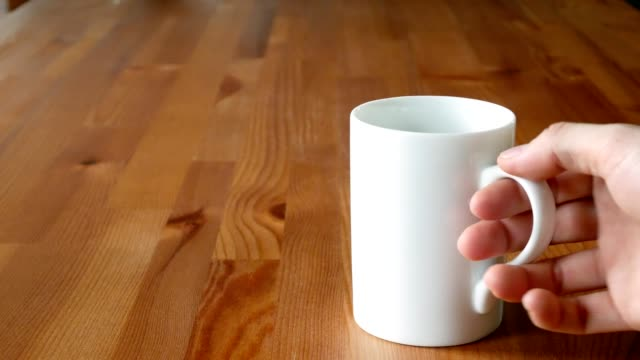 man hand stirring coffee in a cup with teaspoon on wooden table video