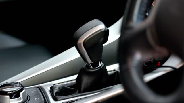 mannen hand byta växelspak i bil. föraren. transport - växelspak bildbanksvideor och videomaterial från bakom kulisserna