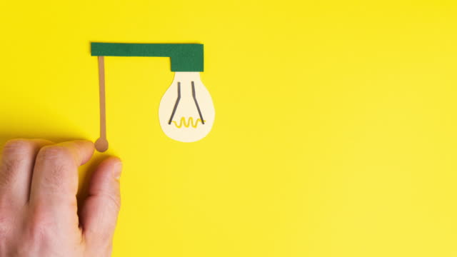 Man hand turns on incandescent light bulb, stop motion animation. Paper art. Business concept.
