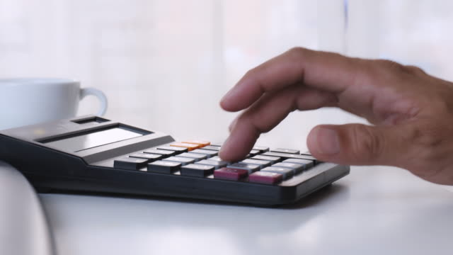 4K man hand using calculator on office desk. Male hand press calculator. Business Man hand using calculator at office. Family budget calculation on wood table.