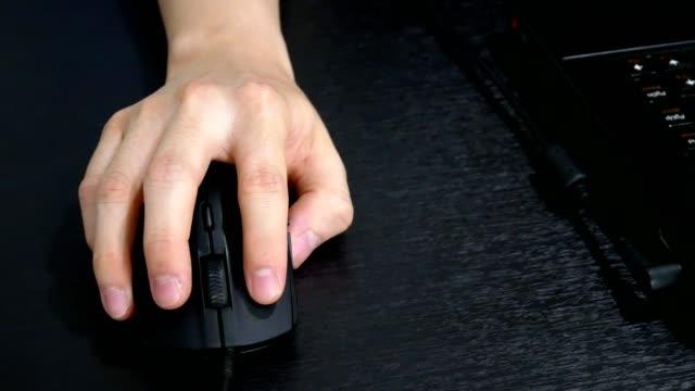 vídeos de stock, filmes e b-roll de homem de mão usando o mouse do computador e trabalhar com o computador portátil na mesa de escritório - close-up vista - log on