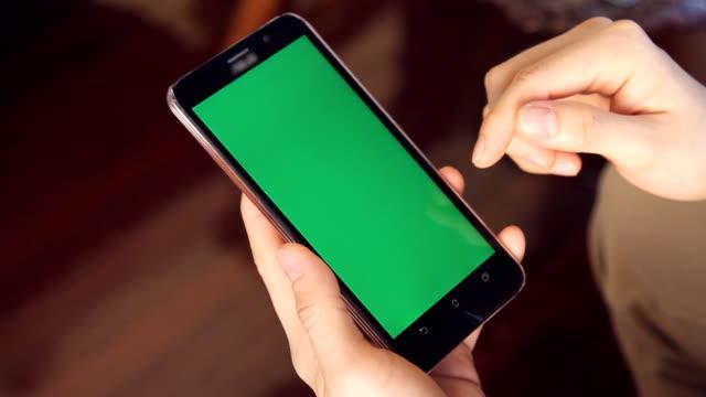 hand des mannes über mobiltelefon mit grünen bildschirm im wohnzimmer - schriftrolle stock-videos und b-roll-filmmaterial