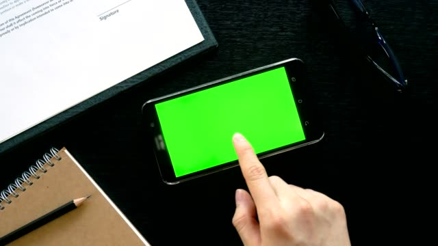 man hand using mobile phone with green screen on office table - top view video