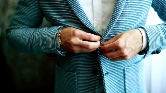 Man hands buttoning casual outfit jacket close up. Stylish well-dressed man trying on blue striped suit preparing to go out. Macho luxury fit size garment golden youth style establishment concept video