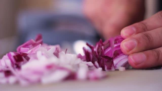 vídeos y material grabado en eventos de stock de manos de hombre cortando cebolla morada en el primer plano de la cocina - comida española