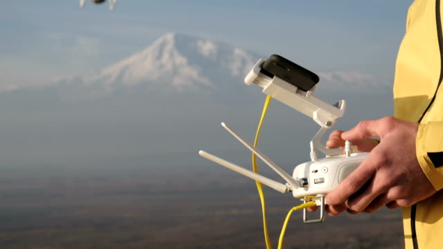 man hands control flying quadcopter near mountain - telecomando background video stock e b–roll
