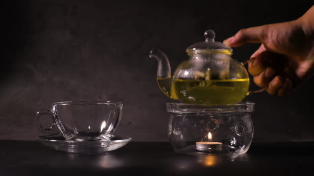 man hands holding teapot and pouring hot green tea into tea cup on kitchen. classic teapot made from glass and boil water by candle. hot drink and tea time concept.