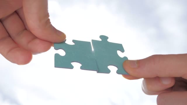 Man hands holding two pieces of puzzle. Finding the solution. Poblem solving background. Teamwork concept. Connection of jigsaw puzzles. Two pieces of puzzle join together. Perfectly fit to each other Man's hand holding and connecting jigsaw puzzles. Business solutions, connection, achievement, and strategy concept. Business concept, jigsaw puzzle shows cooperation, unity will lead to success mental wellbeing stock videos & royalty-free footage