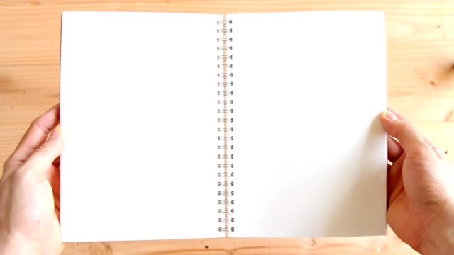man hands opening empty blank notebook on wooden background - use for template
