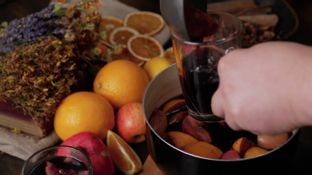 Man hands pour mulled wine in to clear glass mug. Fresh lemons, oranges, pomegranate and dried herbs in background. Steam from wine soar over the saucepan. Close up top view.