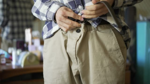 Man Hands Puts On Casual Trousers Pants Or Shorts And Tight
