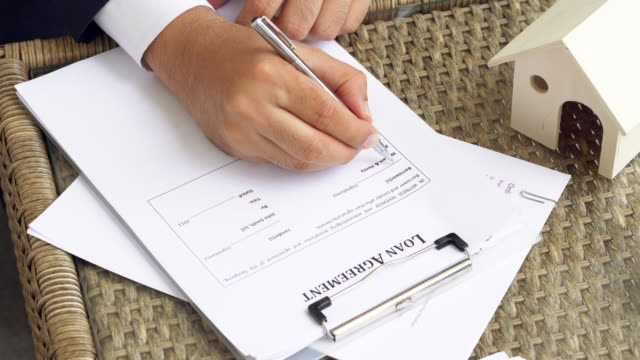 Man hands putting signature on document loan agreement, contract for buy new house.