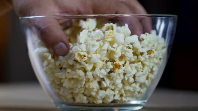 stockvideo's en b-roll-footage met man handen nemen popcorn uit de glazen kom, kijken naar tv-shows en eten - popcorn