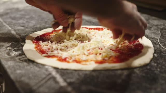 Man hands topping the pizza with cheese video