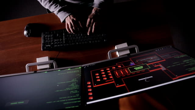 TOP VIEW. Man hands typing on a keyboard in a dark room. Hacker, it professional, computer specialist at work. Unrecognizable video