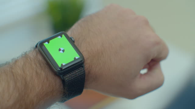 Man hands use smartwatch with green screen chromakey content touch display communication close up.