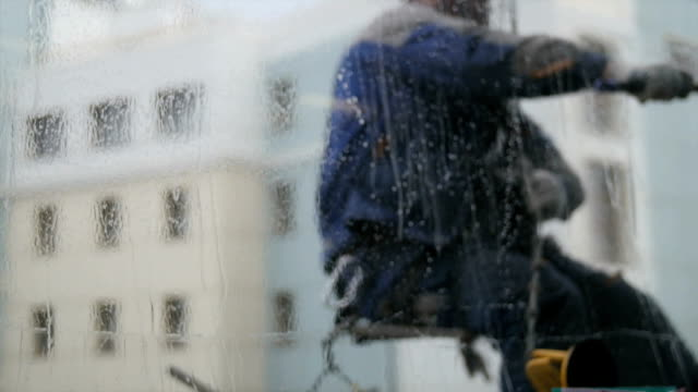 A man hanging on a wall and washing window. Blurred veiw through the glass video