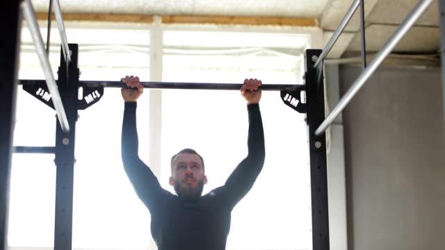バー、ジムでワークアウト トレーニング中の運動を引っ張って男ことに掛かっている男 - ウエイトトレーニング点の映像素材/bロール