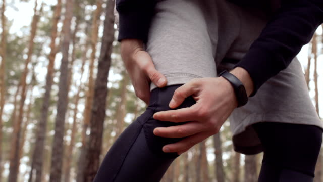 Man has a pain in knee, but continue to run in the forest Man stands in front of camera and holding by his knee. The sportsman suffers from pain in his leg, but continue his train in the forest. knee stock videos & royalty-free footage