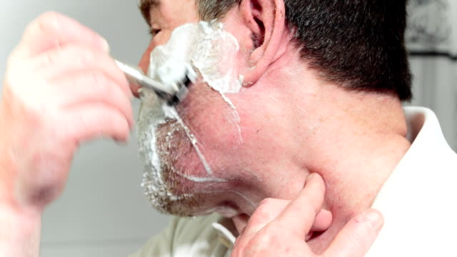 Man has a shave with the razor a side view video