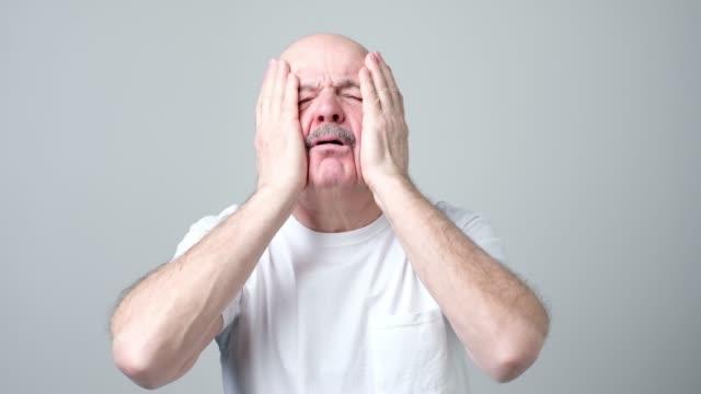 man has headache, feels tired, tries to concentrate - maglietta bianca video stock e b–roll
