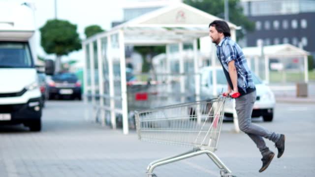 man har kul på parkering shopping mall. glad rolig kille rider på kundvagn. kund med shopping vagn nära supermarket - köpnarkoman bildbanksvideor och videomaterial från bakom kulisserna