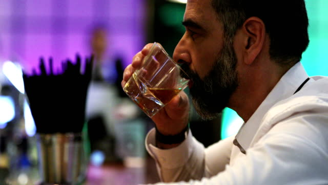 man having a drink in a bar. - alchol video stock e b–roll
