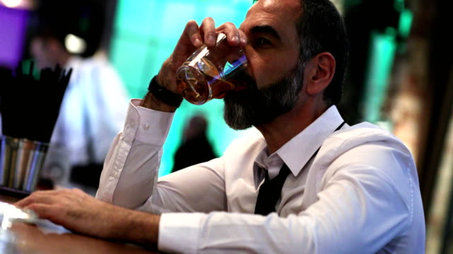 Man having a drink in a bar. Closeup side view of a late 40's businessman having a bourbon drink at a local bar after a long day at work.  He's sitting at a bar counter and is totally disconnected, slowly sipping his drink. 4k video. bar counter stock videos & royalty-free footage
