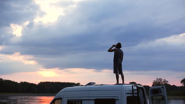 Man having a drink on top of his caravan at sunset