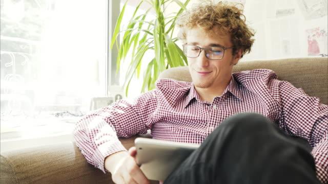 stockvideo's en b-roll-footage met man met een video-oproep op digitale tablet. - blond curly hair