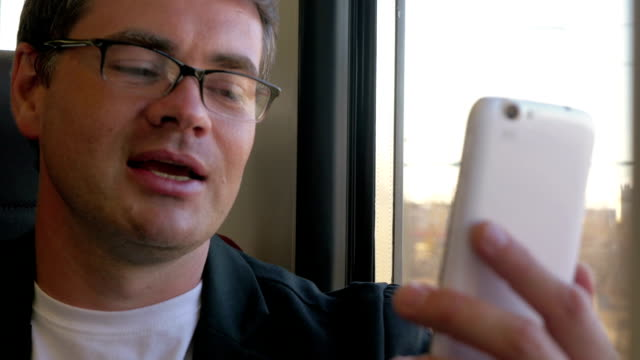 Man having a video chat on mobile during train ride video