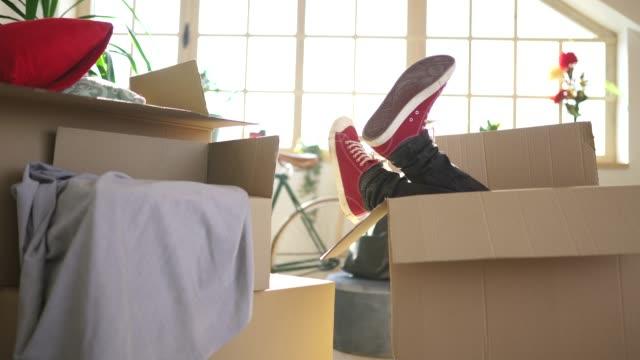 vídeos de stock e filmes b-roll de man having fun in cardboard box in his new home - cardboard box