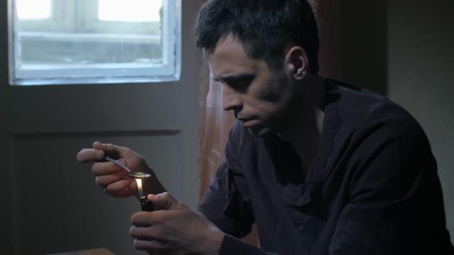 stockvideo's en b-roll-footage met mens die heroïnedosis in lepel met aansteker verwarmt - amfetamine