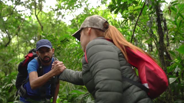 Man helping friend during hiking in a forest video