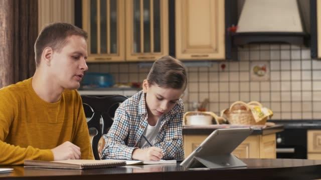 mannen att hjälpa sonen att göra läxor - parent talking to child bildbanksvideor och videomaterial från bakom kulisserna